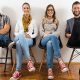 four people smiling and sitting with legs crossed