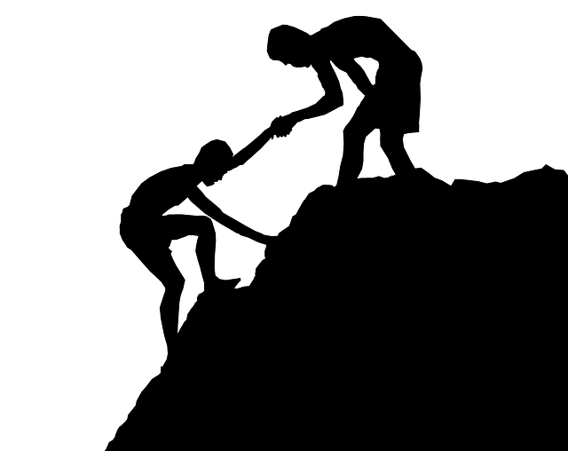 someone helping another person climb a mountain